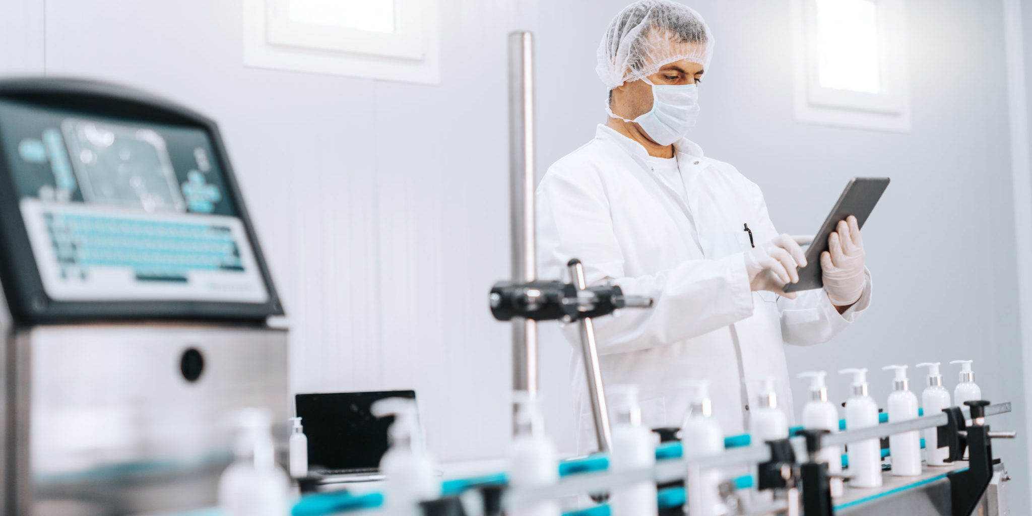 Portrait of Caucasian chemist in sterile uniform using tablet while standing next to machine with liquid soaps. Chemical factory interior.